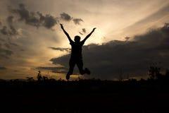 Силуэт скакать женщины Стоковая Фотография