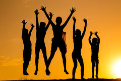 Силуэт 5 скача детей против захода солнца стоковое изображение rf