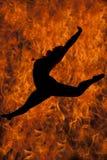 Силуэт скачки танцев женщины в огне Стоковые Изображения RF