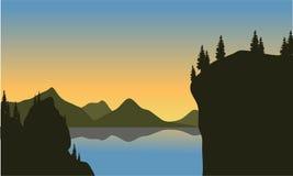Силуэт скалы на озере Стоковые Фото