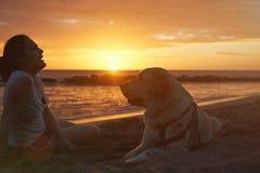 Силуэт смеясь над девушки с собакой labrador Стоковые Фотографии RF