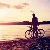 Силуэт спортсмена держа велосипед на bech озера, красочном облачном небе захода солнца и отражении в волнистом уровне воды Стоковое Изображение