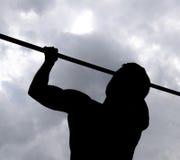 Силуэт спортсмена на баре Человек вытягивает вверх на баре Играть спорт в свежем воздухе Турник Стоковые Фотографии RF
