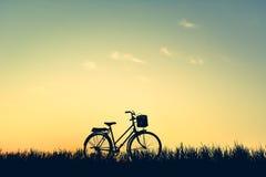 Силуэт старого велосипеда на траве с заходом солнца неба Стоковая Фотография RF
