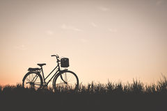 Силуэт старого велосипеда на траве с заходом солнца неба Стоковые Фото