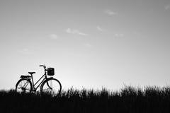 Силуэт старого велосипеда на траве Стоковая Фотография RF