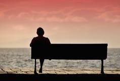 Силуэт старшей женщины сидя самостоятельно на стенде Стоковые Фото