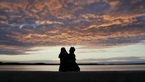 Силуэт стильной молодой пары в влюбленности сидя на прогулке небом захода солнца моря красивым на предпосылке видеоматериал