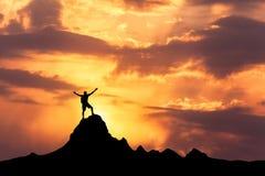 Силуэт стоящего счастливого человека на горном пике Стоковое Изображение