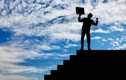 Силуэт счастливого бизнесмена на лестницах Стоковые Изображения RF