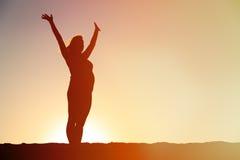 Силуэт счастливой беременной женщины на заходе солнца стоковое изображение