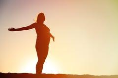 Силуэт счастливой беременной женщины на заходе солнца стоковые фотографии rf