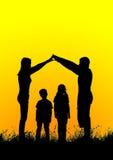 Силуэт счастливой семьи делая домашний знак на заходе солнца Стоковые Изображения