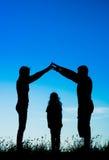 Силуэт счастливой семьи делая домашний знак Стоковое фото RF