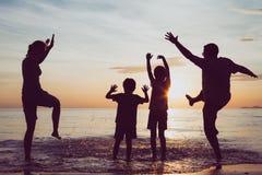 Силуэт счастливой семьи который играя на пляже на sunse Стоковое Изображение