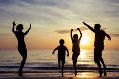 Силуэт счастливой семьи который играя на пляже на sunse Стоковая Фотография RF