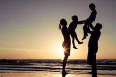 Силуэт счастливой семьи который играя на пляже на sunse Стоковые Изображения RF