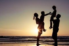 Силуэт счастливой семьи который играя на пляже на sunse Стоковые Фото
