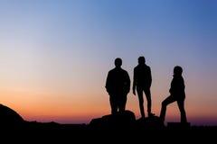 Силуэт счастливой семьи с оружиями поднял вверх против красивого неба за валами 2 захода солнца лета сосенки стоящими Стоковые Фото