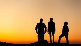Силуэт счастливой семьи с оружиями поднял вверх против красивого неба за валами 2 захода солнца лета сосенки стоящими Стоковые Изображения