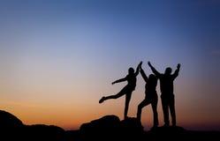 Силуэт счастливой семьи с оружиями поднял вверх против красивого неба за валами 2 захода солнца лета сосенки стоящими Стоковое Изображение RF