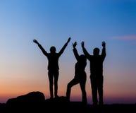 Силуэт счастливой семьи с оружиями поднял вверх против красивого неба за валами 2 захода солнца лета сосенки стоящими Стоковые Изображения RF