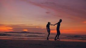 Силуэт счастливых любящих пар встречает и играет на пляже на заходе солнца в береге океана сток-видео