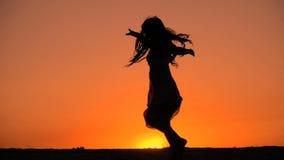 Силуэт танцев маленькой девочки на заходе солнца