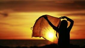Силуэт танцев hijab девушки нося во время захода солнца Стоковые Фото