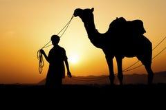 Силуэт торговца верблюда пересекая песчанную дюну Стоковая Фотография RF