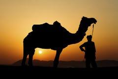 Силуэт торговца верблюда пересекая песчанную дюну Стоковые Изображения RF