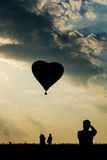 Силуэт туриста человека принимая фото воздушного шара формы сердца горячего Стоковое Изображение RF