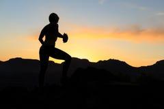 Силуэт успеха женщины взбираясь в заходе солнца гор Стоковое Фото