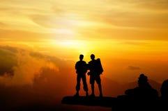 Силуэт успеха женщины на верхней горе на заходе солнца, селективный Стоковое Изображение RF