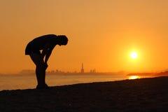 Силуэт утомленного спортсмена на заходе солнца Стоковая Фотография RF