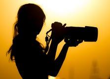 Силуэт фотографа девушки на заходе солнца Стоковое Изображение