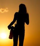 Силуэт фотографа девушки на заходе солнца Стоковые Изображения RF