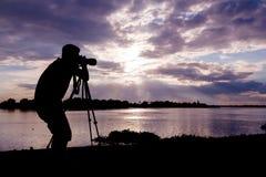 Силуэт фотографа на заходе солнца стоковое фото rf