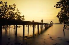 Силуэт фотографа на моле во время захода солнца стоковые фото