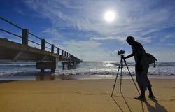 Силуэт фотографа снимая деревянный мост после su стоковое фото