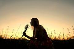 Силуэт цветков рудоразборки девушки в луге на заходе солнца Стоковая Фотография RF