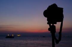 Силуэт цифровой фотокамера на треноге с небом на море bl захода солнца Стоковая Фотография