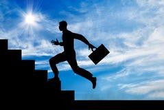 Силуэт человека бежать вверх лестницы Стоковая Фотография