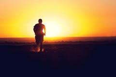 Силуэт человека бежать в поле Стоковые Фотографии RF