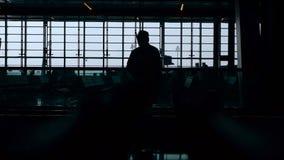 Силуэт человека в шляпе которая едет на эскалаторе на авиапорте Большое окно на предпосылке самомоднейше сток-видео