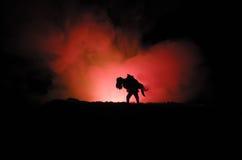 силуэт человека держа дальше к женщине Концепция спасителя спасения Избежание от огня или опасности Часы, огонь стоковая фотография