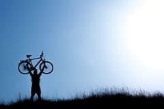 Силуэт человека держа велосипед на голубом небе Стоковое фото RF