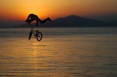 Силуэт человека делая скачку с велосипедом Стоковые Фото