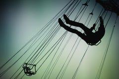 Силуэт человека имея потеху на carousel Стоковое Изображение