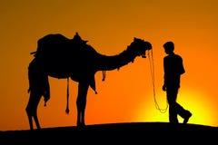 Силуэт человека и верблюда на заходе солнца в пустыне, Jaisalmer - Индии Стоковое Фото